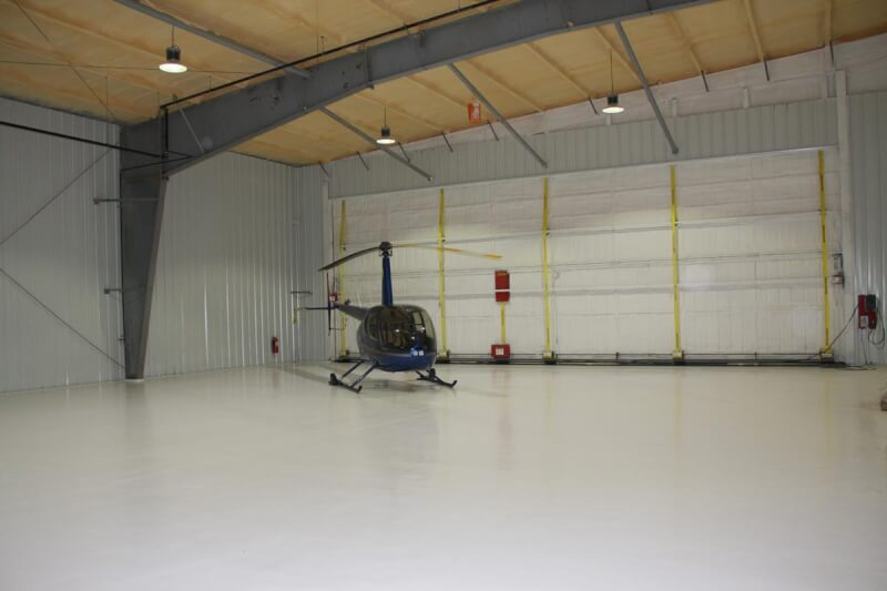 helicopter inside steel building with wide opening door